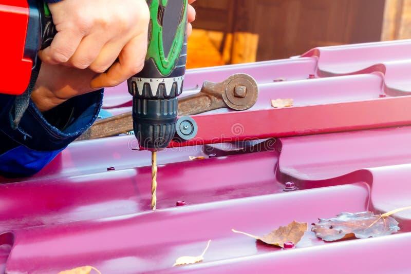 As mãos masculinas furam um furo no telhado para o parafuso com uma chave de fenda Reparo do telhado imagem de stock royalty free