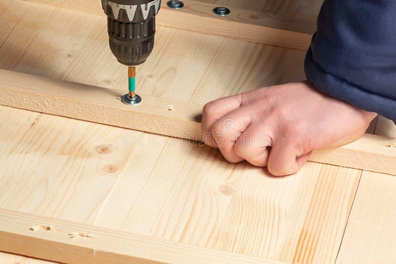 As mãos masculinas parafusam blocos de madeira às placas com uma chave de fenda foto de stock
