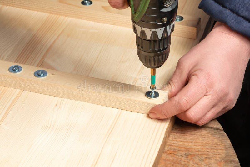 As mãos masculinas parafusam blocos de madeira às placas com uma chave de fenda imagem de stock