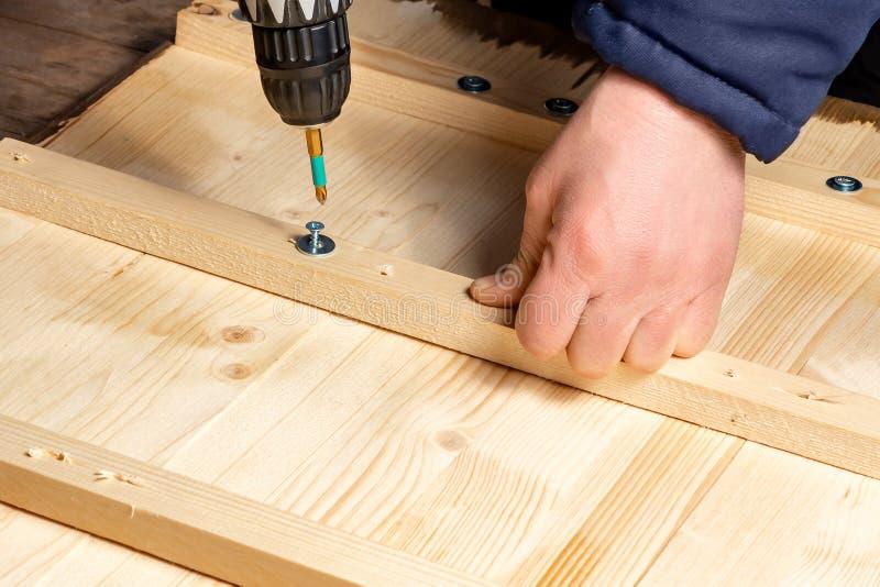 As mãos masculinas parafusam blocos de madeira às placas com uma chave de fenda imagens de stock royalty free
