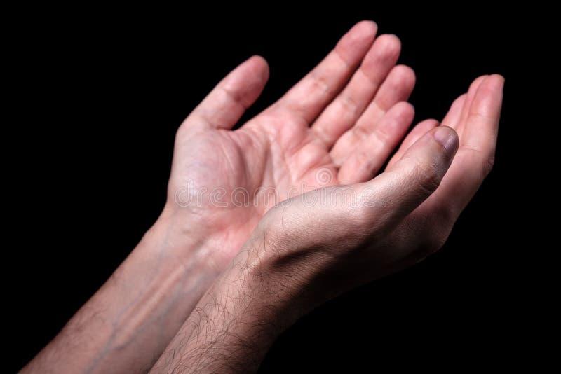 As mãos masculinas que rezam com palmas levantam os braços estendido Fundo preto imagens de stock royalty free