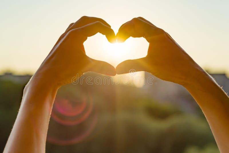 As mãos mostram o gesto ao coração, por do sol da noite do fundo, silhueta da cidade fotos de stock royalty free