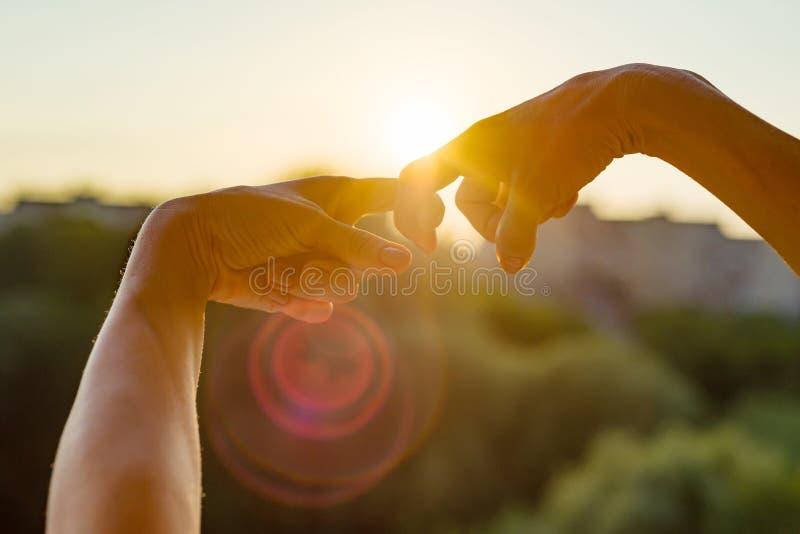 As mãos mostram o gesto dos dedos junto, o símbolo da amizade e o relacionamento Por do sol da noite do fundo, silhueta da cidade fotografia de stock royalty free