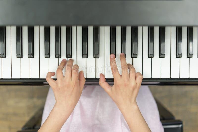 As mãos no piano fecham o close-up A mão da menina do close up que joga o piano Música clássica favorita Vista superior com vinhe imagens de stock