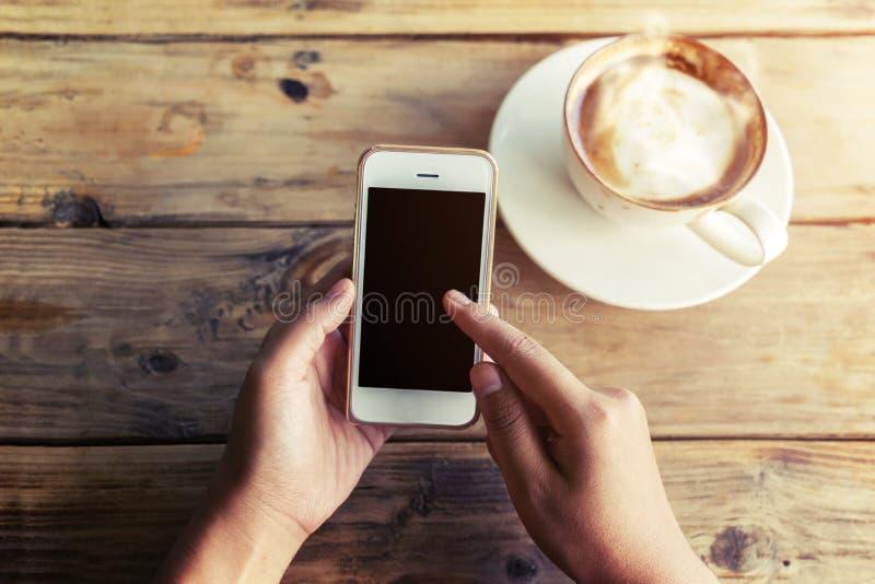 As mãos novas bonitas do ` s da mulher do moderno que guardam o telefone esperto móvel com o copo de café quente no café compram, fotos de stock royalty free
