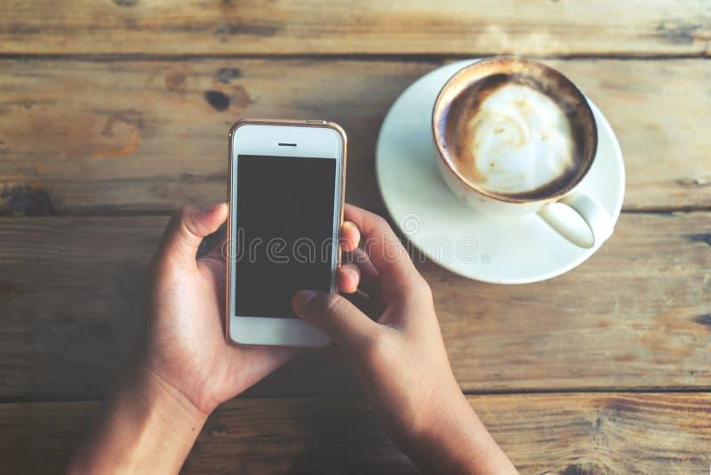 As mãos novas bonitas do ` s da mulher do moderno que guardam o telefone esperto móvel com o copo de café quente no café compram, fotos de stock