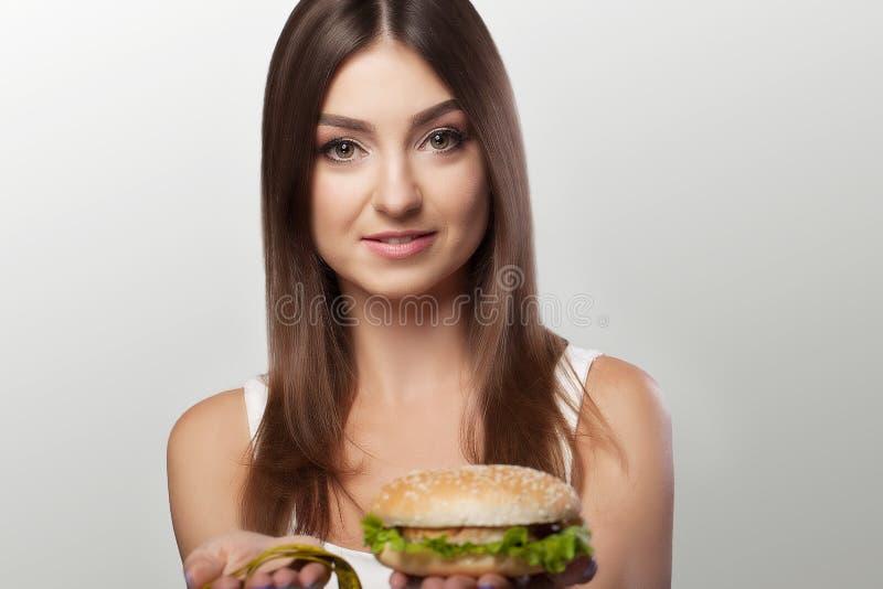 As mãos oferecem a uma maçã o alimento e bolos saudáveis o alimento insalubre t imagens de stock royalty free