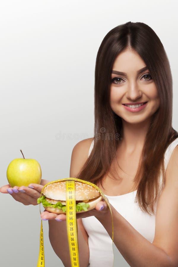 As mãos oferecem a uma maçã o alimento e bolos saudáveis o alimento insalubre t fotografia de stock royalty free