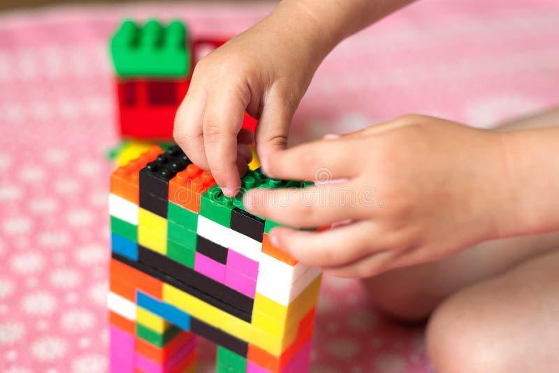 As mãos pequenas da criança recolhem o desenhista colorido plástico brilhante Brinquedos educacionais e cedo aprendizagem imagem de stock royalty free
