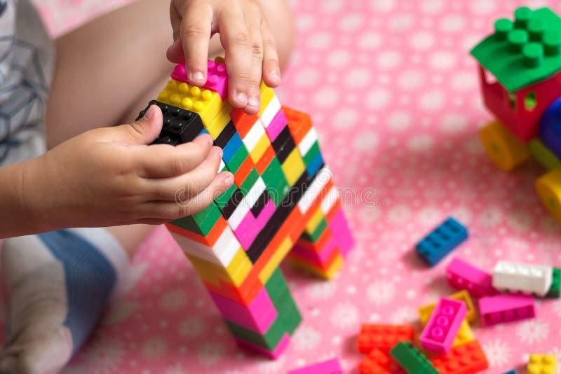 As mãos pequenas da criança recolhem o desenhista colorido plástico brilhante Brinquedos educacionais e cedo aprendizagem fotografia de stock