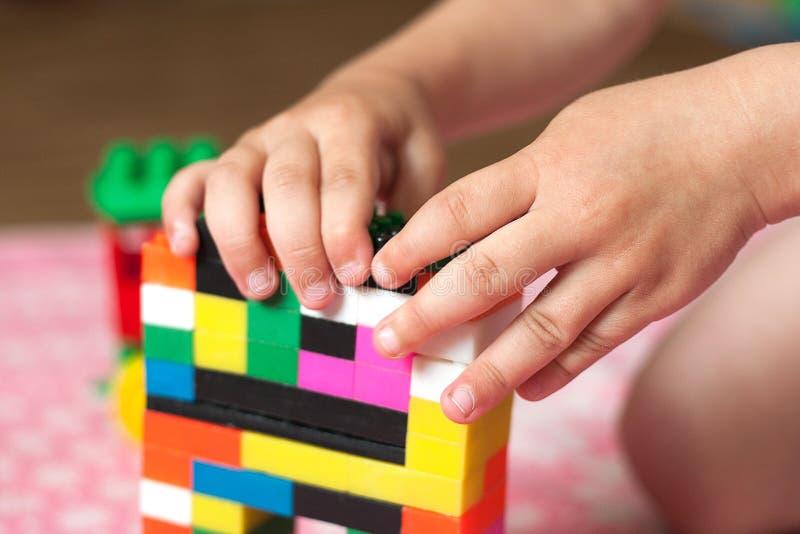As mãos pequenas da criança recolhem o desenhista colorido plástico brilhante Brinquedos educacionais e cedo aprendizagem foto de stock royalty free