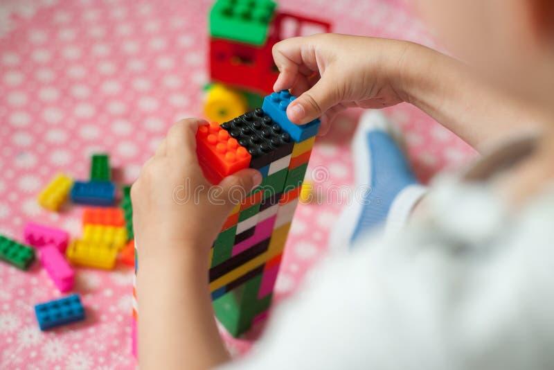 As mãos pequenas da criança recolhem o desenhista colorido plástico brilhante Brinquedos educacionais e cedo aprendizagem foto de stock