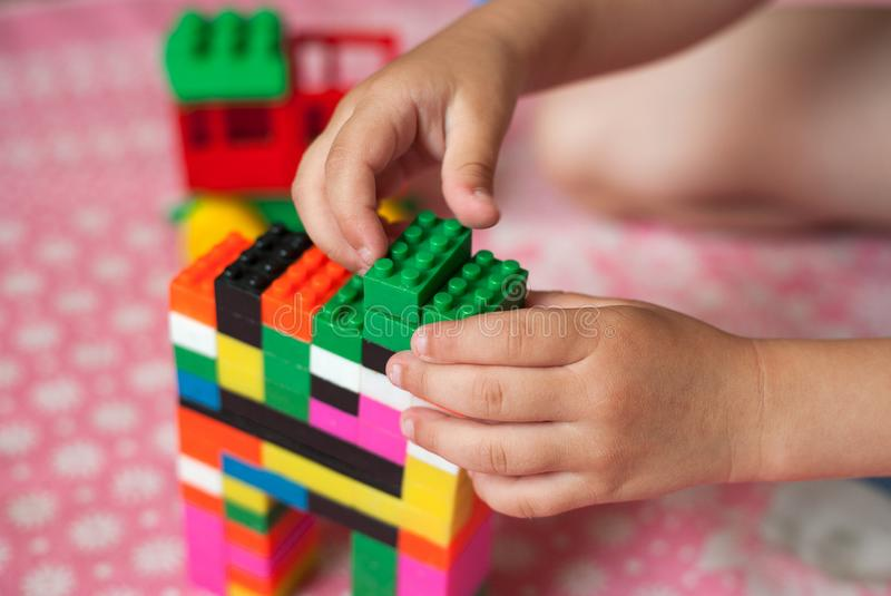 As mãos pequenas da criança recolhem o desenhista colorido plástico brilhante Brinquedos educacionais e cedo aprendizagem fotos de stock