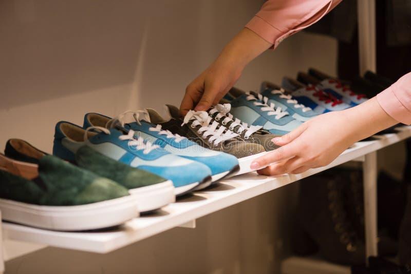 As mãos puseram a coleção das sapatilhas sobre a cremalheira da loja fotografia de stock