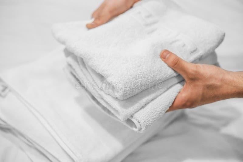 As mãos puseram as toalhas brancas sobre uma cama branca Neg?cio do hotel imagem de stock