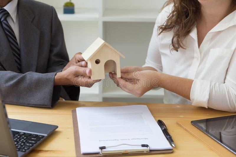 As mãos que dão a casa modelam a outras mãos com acordo na mesa fotos de stock