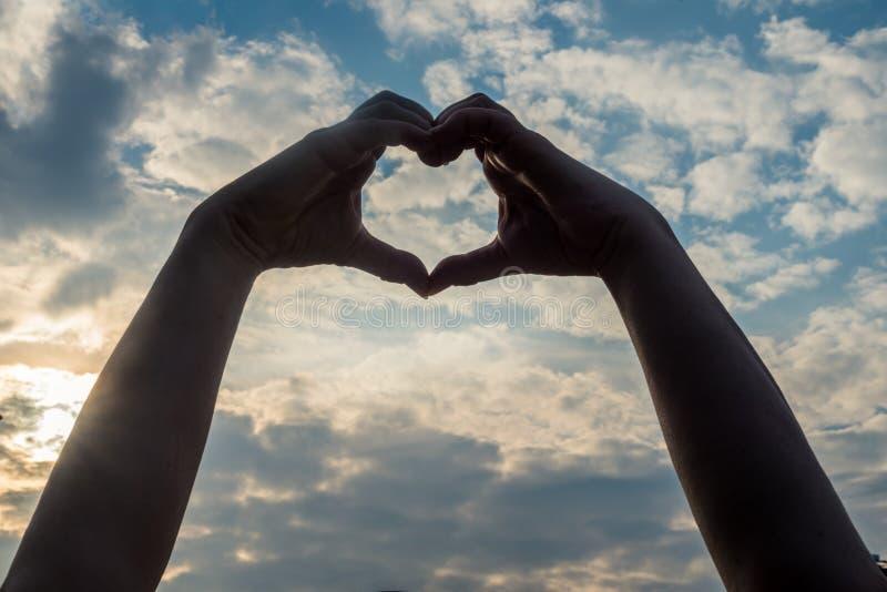 As mãos que formam um coração - espalhe o amor fotografia de stock