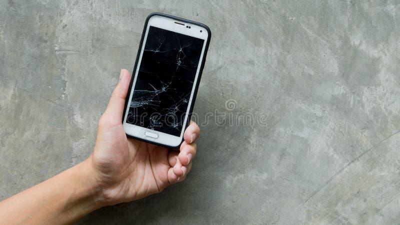 As mãos que guardam o Smart-telefone quebrado do moblie focalizaram no muro de cimento imagem de stock royalty free