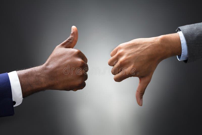 As mãos que mostram os polegares acima e os polegares assinam para baixo imagem de stock royalty free