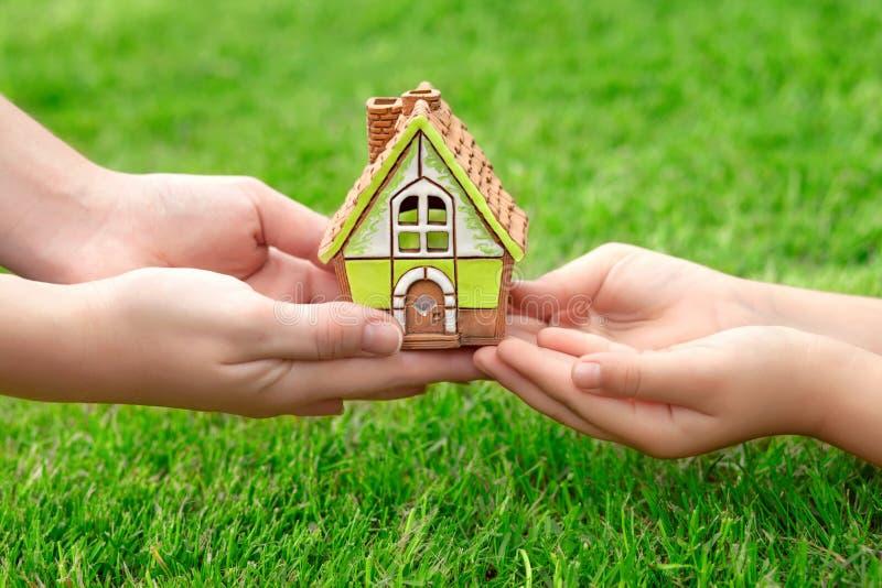As mãos serem de mãe e uma criança que guarda uma casa pequena em um fundo fotografia de stock royalty free