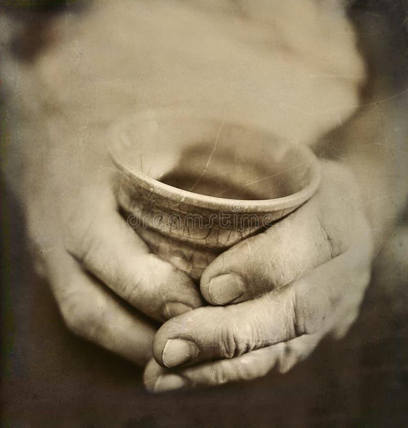 As mãos vestidas do homem que guardam copo cerâmico japonês rachado fotografia de stock