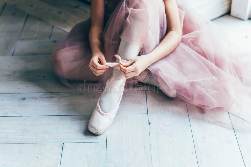 As m?os da bailarina p?em sapatas do pointe sobre o p? na classe de dan?a foto de stock royalty free