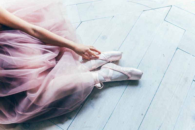 As m?os da bailarina p?em sapatas do pointe sobre o p? na classe de dan?a fotografia de stock