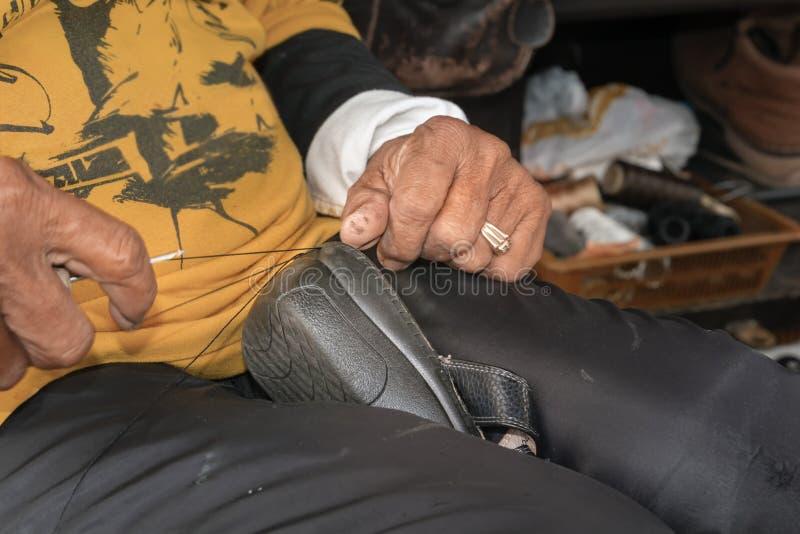 As m?os de um sapateiro costuram sand?lias velhas na loja da rua fotografia de stock
