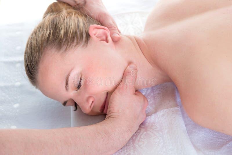 As m?os do ` s dos homens fazem uma massagem terap?utica do pesco?o para uma menina que encontra-se em um sof? da massagem em uns imagem de stock