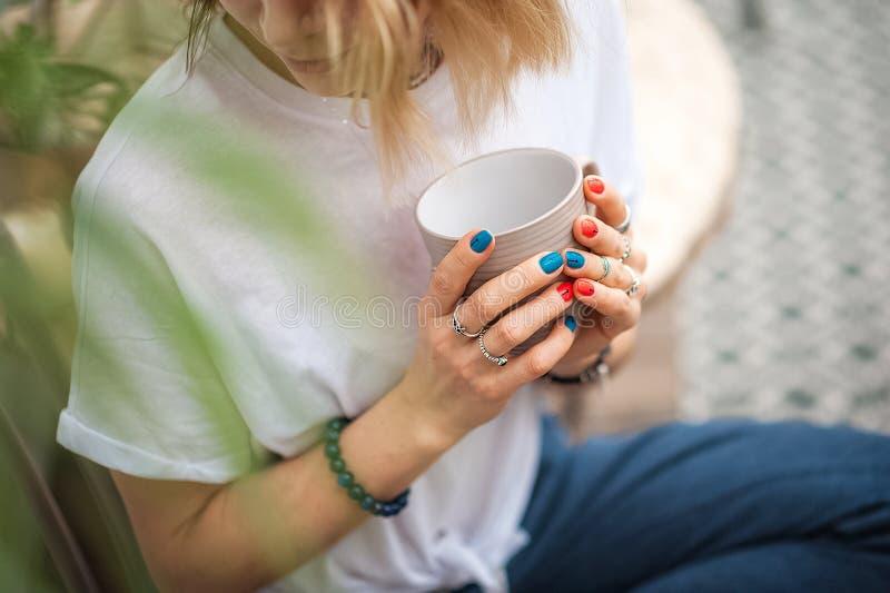 As m?os do toque da menina a joia feito a m?o Menina e um copo Mulher feito a mão que decora pedras close up, meditação, manhã, t imagens de stock royalty free