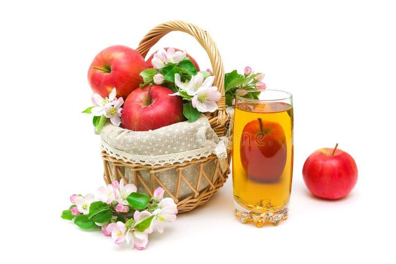 As maçãs, um vidro do suco e a maçã florescem em um fundo branco foto de stock royalty free
