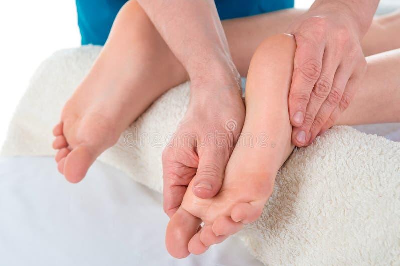 As massagens manuais masculinas de um terapeuta profissional da massagem e esticam os pés e os pés do paciente das mulheres Terap imagens de stock royalty free