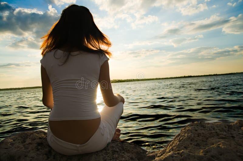 As meditação da menina aproximam a água imagens de stock