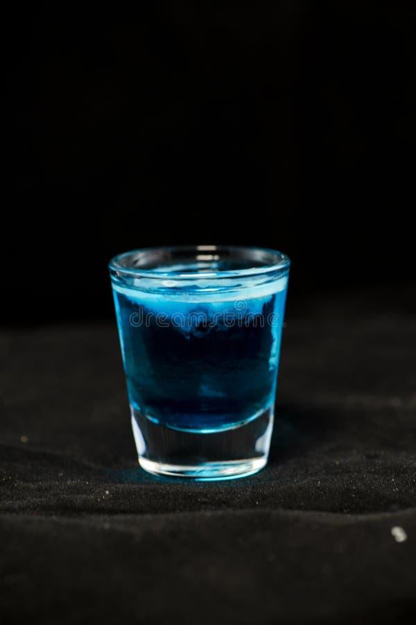As medusa dispararam no cocktail com Curaçau, o sambuca, vodca e leite azuis imagens de stock royalty free