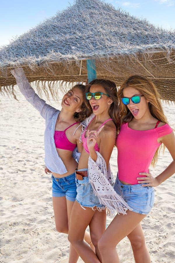 As meninas adolescentes dos melhores amigos cobrem com sapê abaixo o guarda-chuva fotografia de stock