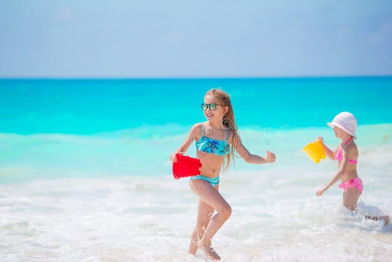 As meninas adoráveis têm o divertimento junto na praia tropical branca foto de stock