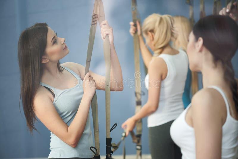 As meninas atrativas do ajuste estão ajustando o equipamento no gym fotografia de stock royalty free