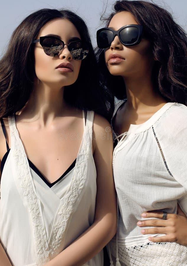As meninas bonitas com cabelo escuro vestem a roupa e óculos de sol elegantes ocasionais foto de stock royalty free