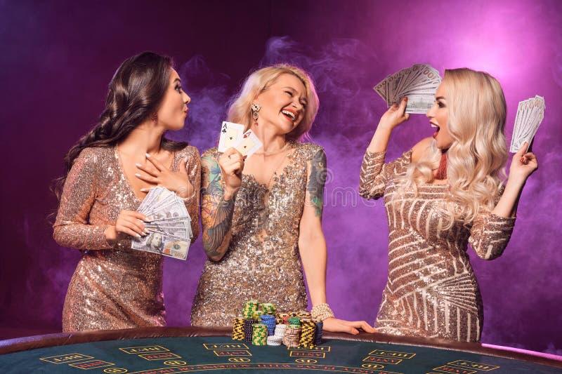 As meninas bonitas com os penteados perfeitos e composição brilhante estão levantando a posição em uma tabela de jogo Casino, p?q foto de stock royalty free