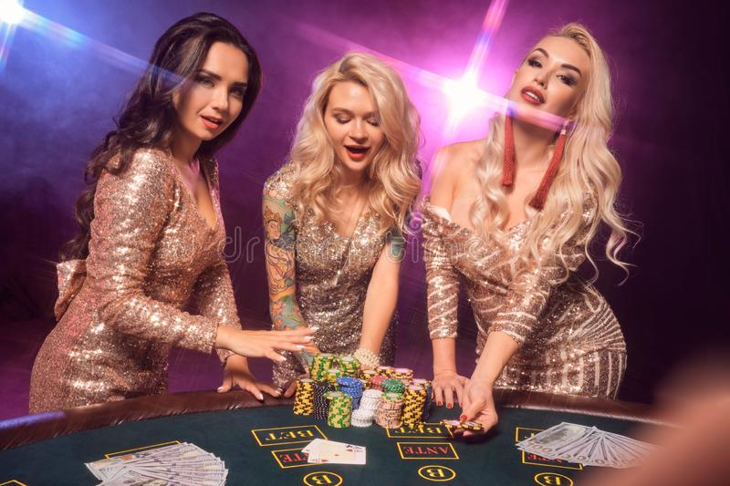 As meninas bonitas com os penteados perfeitos e composição brilhante estão levantando a posição em uma tabela de jogo Casino, p?q imagem de stock