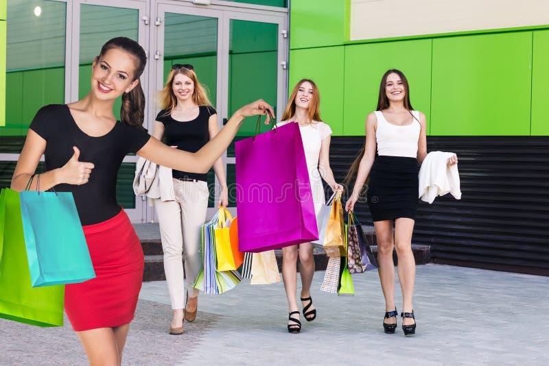 As meninas bonitas com sacos de compras aproximam a alameda fotografia de stock