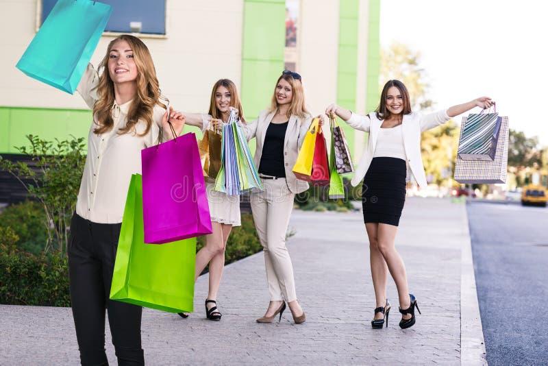 As meninas bonitas com sacos de compras aproximam a alameda imagem de stock