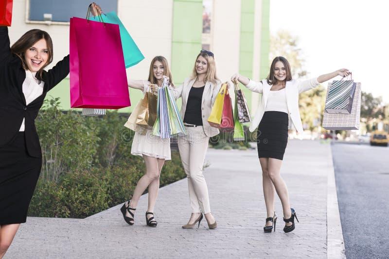 As meninas bonitas com sacos de compras aproximam a alameda imagem de stock royalty free