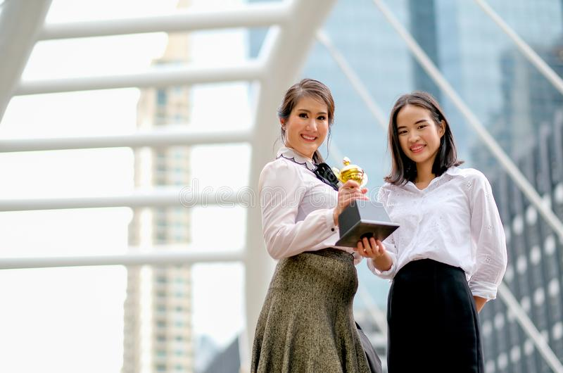 As meninas bonitas do negócio mostram seu troféu do sucesso em seus trabalhos e estão entre a construção alta na cidade imagens de stock