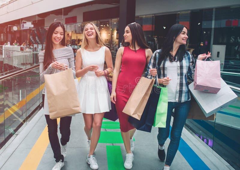 As meninas bonitas estão andando junto na alameda Estão comprando As jovens mulheres têm sacos em suas mãos As meninas estão rind fotografia de stock