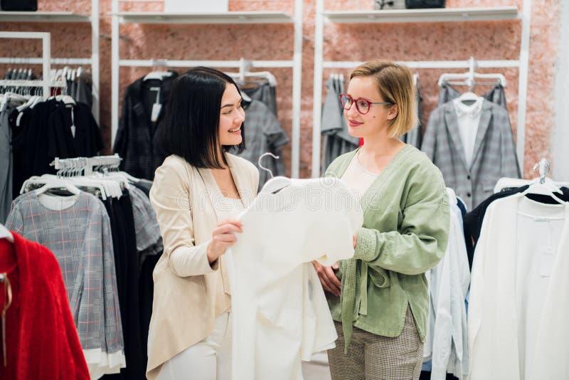 As meninas bonitas estão escolhendo a roupa, estão falando e estão sorrindo ao fazer a compra no boutique foto de stock royalty free