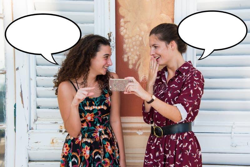 As meninas bonitas estão rindo sobre algo em uma bolha do discurso fotos de stock royalty free