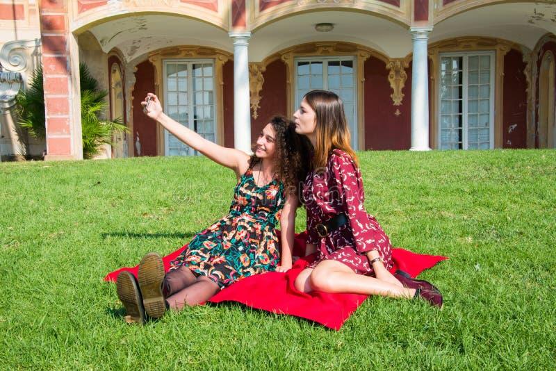 As meninas bonitas estão tomando um selfie com um smartphone imagens de stock
