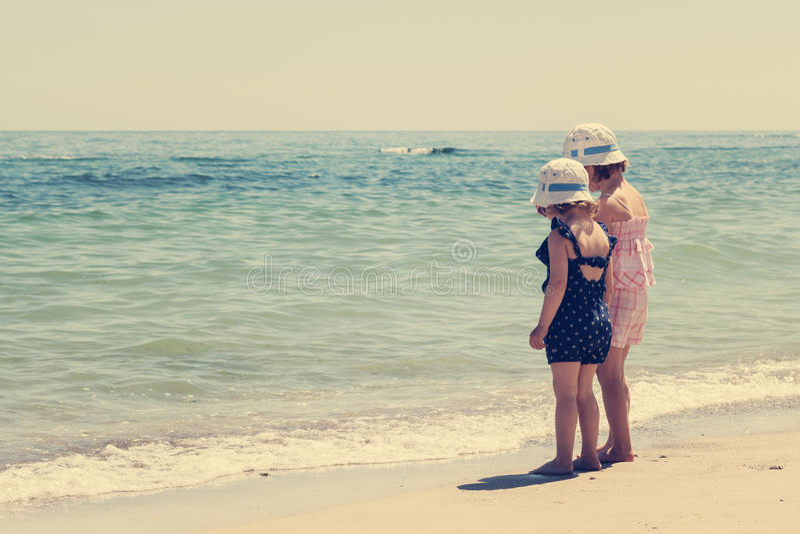 As meninas bonitas (irmãs) estão jogando na praia imagens de stock
