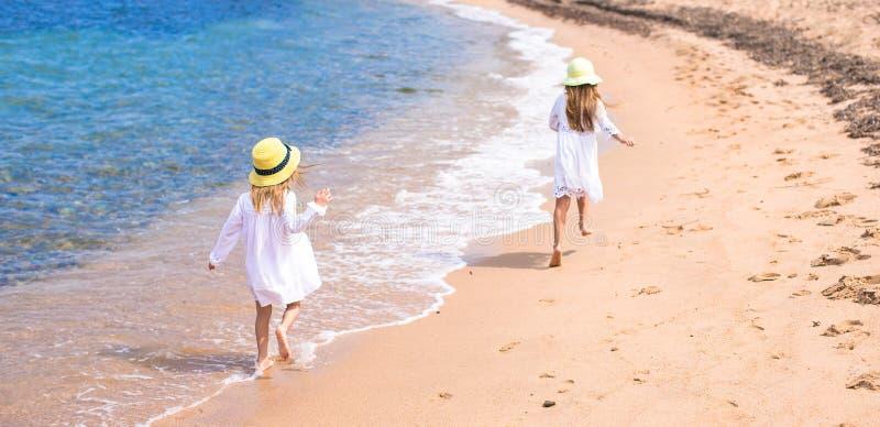 As meninas bonitos adoráveis têm o divertimento na praia branca durante fotos de stock